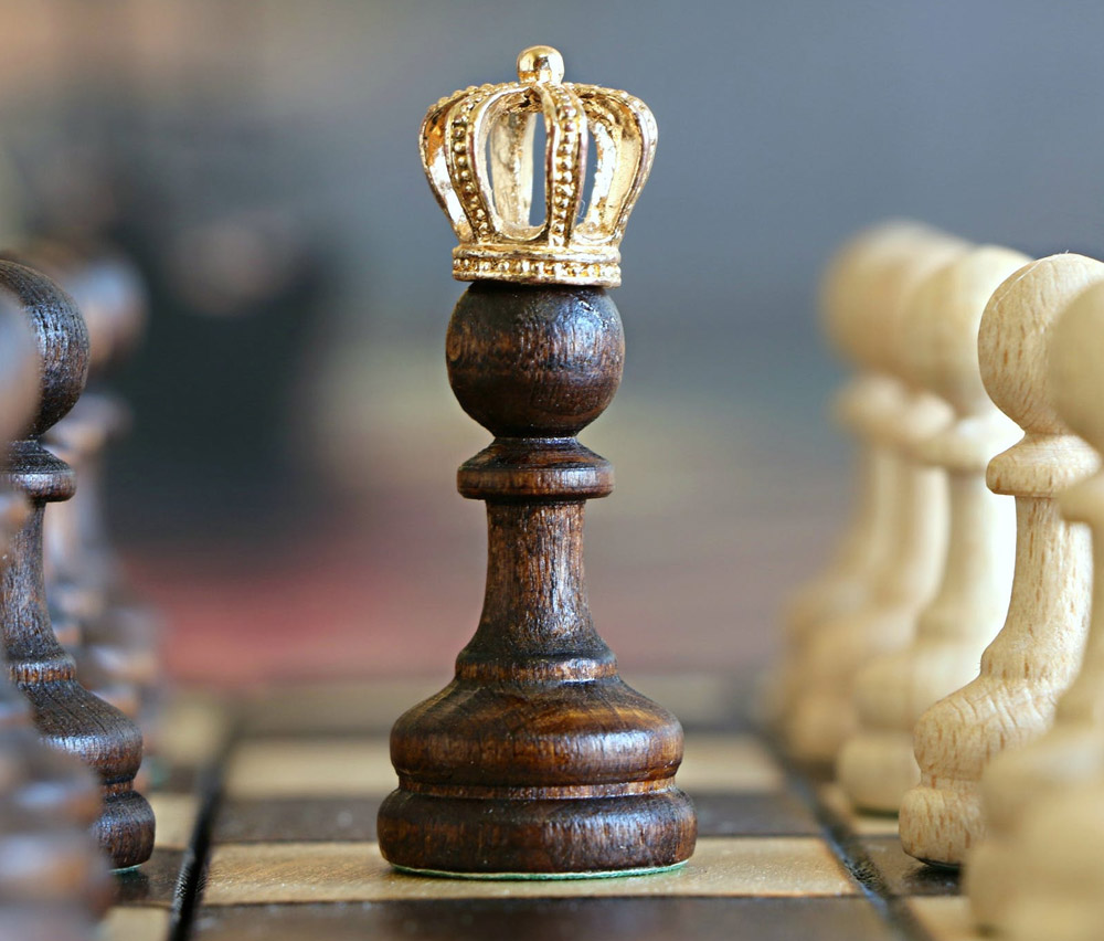 A chess peice with a gold crown on